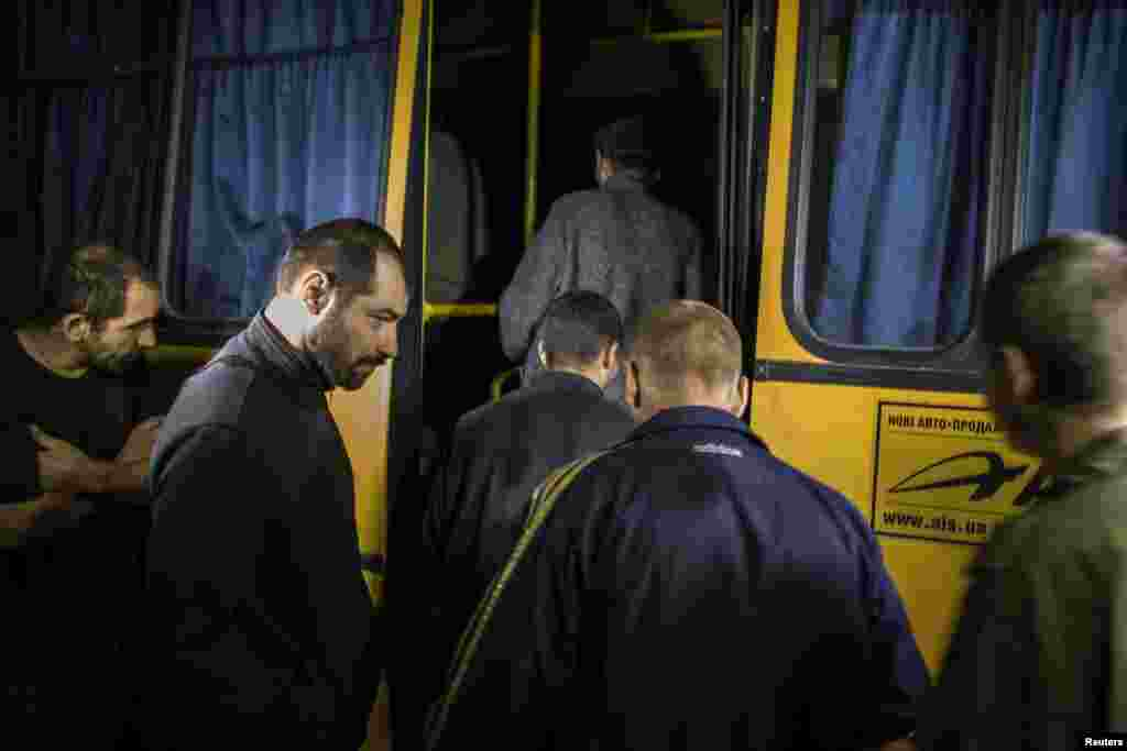 Members of the pro-Russian rebels, who were held as prisoners-of-war, enter a bus after being exchanged, north of Donetsk, eastern Ukraine, Sept. 21, 2014.