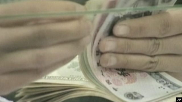 A bank teller counts a stack of US and Chinese currency