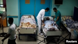 Patients lie in their beds on the ground floor of al-Wafa rehabilitation hospital after being evacuated from the fourth floor, which police said was hit by a tank shell fired by Israeli troops, in Gaza City, July 16, 2014.