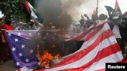 Anggota Front Pembela Islam (FPI) membakar tiruan bendera Amerika dalam unjuk rasa di depan Kedutaan Besar Amerik, di Jakarta, 11 Desember 2017. Para pengunjuk rasa memprotes keputusan Washington untuk mengakui Yerusalem sebagai Ibu Kota Israel