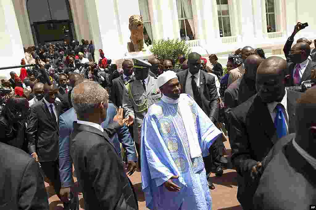 Senegal's outgoing President Abdoulaye Wade, center right, leaves the presidential palace, ceding its occupancy to newly inaugurated leader Macky Sall, in Dakar, Senegal Monday, April 2, 2012. Sall took the oath of office Monday in a ceremony held one wee