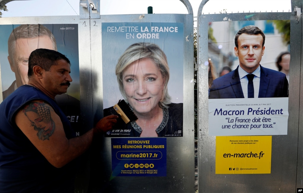 """2017年4月14日,有人走在巴黎街頭,擋住了一位競選人的海報,正好顯示了兩位首輪投票勝利者——法國國民陣線領導人勒龐(女)和""""前進""""運動主席馬克龍的競選海報"""