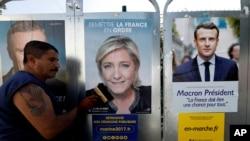"""Fransa Milli Cəbhəsi (FN) lideri Marine Marine Le Pen (ortada) və """"İrəli!"""" hərəkatının rəhbəri Emmanuel Makrona (sağda) məxsus siyasi posterlər. Antibes, Fransa, 14 aprel, 2017."""