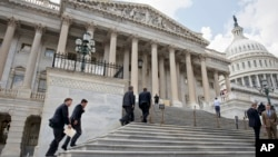 FILE - Members of Congress climb the steps at the Capitol in Washington, July 31, 2014.