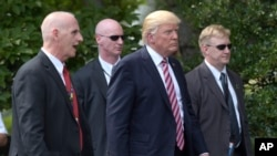 President Donald Trump, his longtime bodyguard Keith Schiller, left, and two Secret Service agents walk along the South Lawn of the White House in Washington, June 12, 2017.