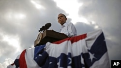 U.S. President Barack Obama is pictured as the sun breaks through clouds at a town hall-style event in Alpha, Illinois, August 17, 2011