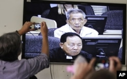 FILE - Journalists take photographs of a television screen showing the trial of Duch, former chief of the S-21 prison, at the Extraordinary Chambers in the Courts of Cambodia (ECCC) on the outskirts of Phnom Penh, Feb. 3, 2012.