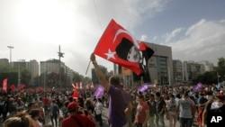 Un homme agite un drapeau portant l'effigie du fondateur de la Turquie Kemal Ataturk alors que des milliers de jeunes se rassemblent à Kizilay Square, Ankara, 2 juin 2013.