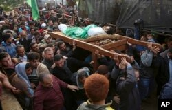 Mourners carry the body of Palestinian fisherman Nawaf Al-Attar, 20, who was shot and killed by Israeli troops on the beach near the border with Israel, during his funeral in Beit Lahiya, northern Gaza Strip, Nov. 14, 2018.