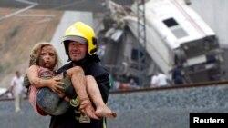 24일 스페인 산티아고 데 콤포스텔라시 고속열차 탈선 사고 현장에서 소방대원이 부상당한 아이를 구조해 나오고 있다.