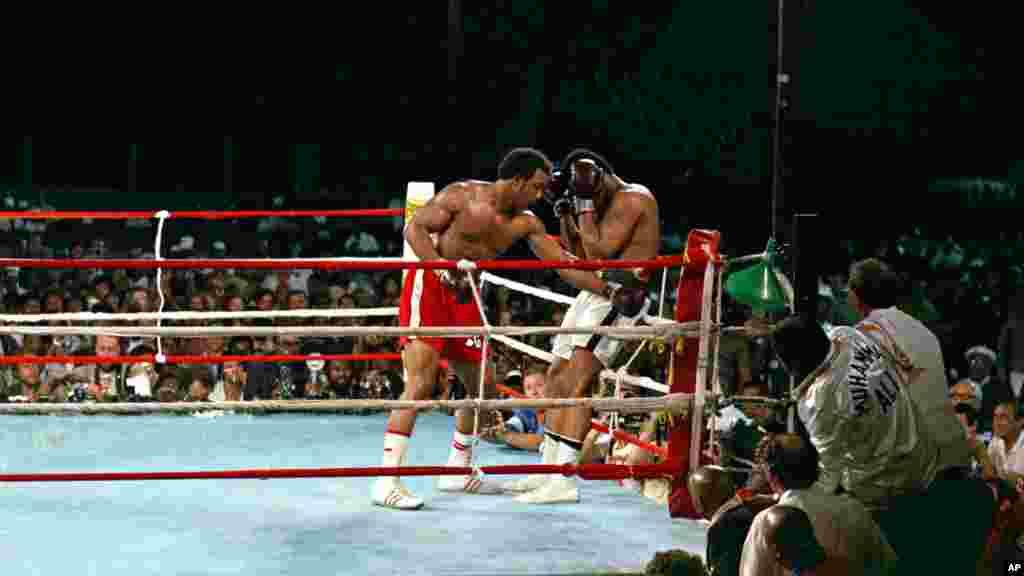 Le champion du monde George Foreman conduit son challenger Muhammad Ali dans les cordes avec un jab de gauche au corps pendant le combat de championnat WBA / WBC à Kinshasa, au Zaïre, le 30 Octobre, 1974. Ali a repris la couronne des poids lourds en assommant Foreman au cours du huitième round de leur combat surnommé «Rumble in the Jungle». (AP Photo)
