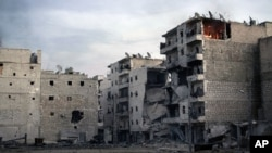 A fire is seen inside an apartment (R) of a damaged building due to heavy fighting between Free Syrian Army fighters and government forces in Aleppo, Syria, December 5, 2012.