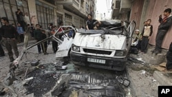 Palestinians inspect the damage to a vehicle after an Israeli air strike in Gaza City April 9, 2011