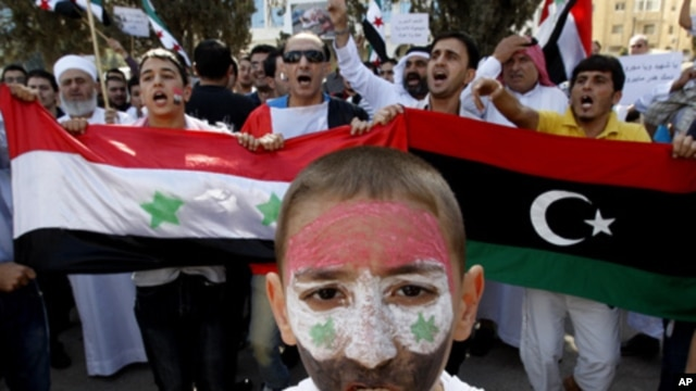 Syrians living in Jordan hold Syrian and the Kingdom of Libya flags shout slogans against Syria's President Bashar al-Assad during a protest outside the United Nations office in Amman October 15, 2011.