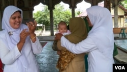 Petugas memberikan imunisasi bagi seorang bayi di Aceh. (VOA/Budi Nahaba)