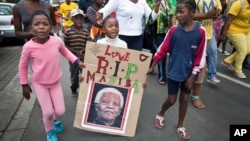 "A young girl with a placard showing the face of Nelson Mandela and referring to his clan name ""Madiba"", marches with others to celebrate his life, in the street outside his old house in Soweto, Johannesburg, South Africa, Dec. 6, 2013."