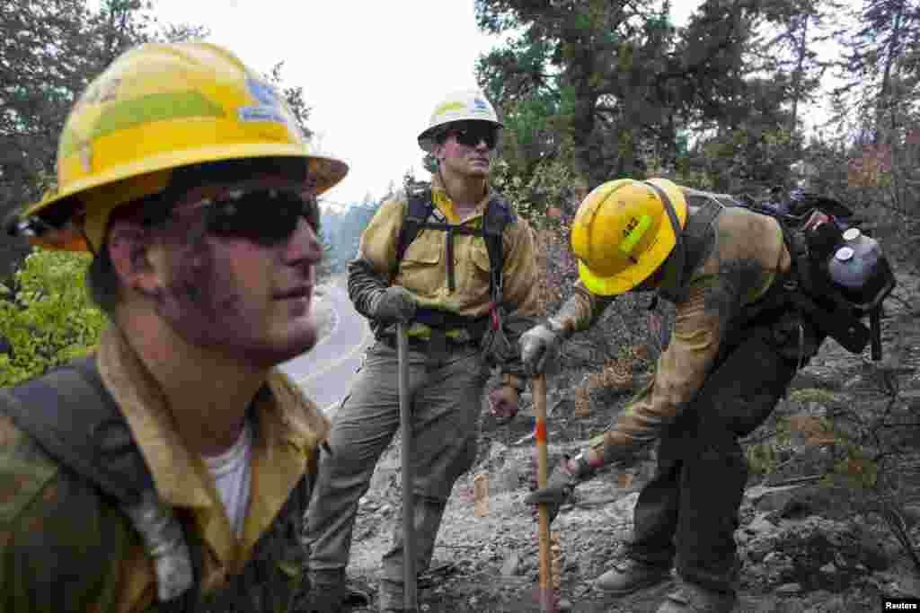 Para petugas memadamkan titik-titik api dengan melakukan penggalian di wilayah yang terbakar di Chelan (24/8). (Reuters/David Ryder)