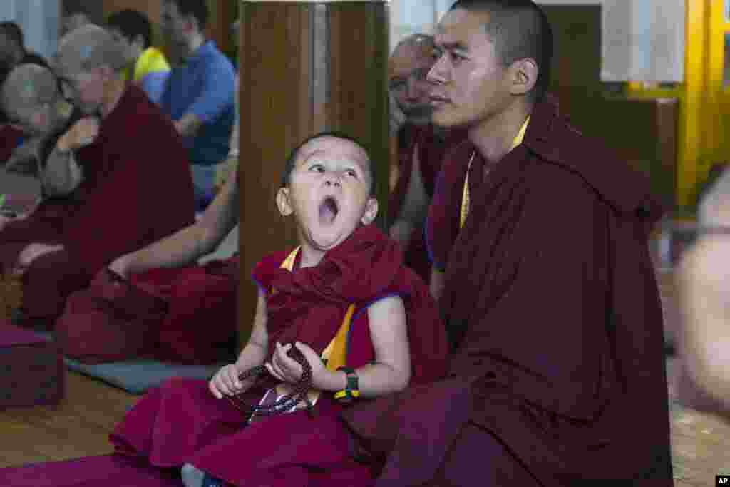 A novice Tibetan Buddhist monk yawns as he sits on the lap of an older monk during a religious talk by their spiritual leader the Dalai Lama at the Tsuglakhang temple in Dharmsala, India.