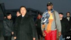 Mantan bintang NBA Dennis Rodman didampingi Wakil Menteri Olahraga Korea Utara, Son Kwang Ho, saat tiba di Pyongyang, Korea Utara (19/12). (AP/Kim Kwang Hyon)