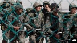 南韓士兵在非軍事區附近演習時走過一道鐵絲網