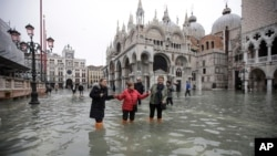 People walk through water in a flooded St. Mark's Square in Venice, Italy, Wednesday, Nov. 13, 2019. The high-water mark hit 187 centimeters late Tuesday, Nov. 12, 2019