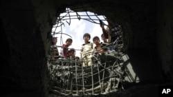 Các bé trai nhìn qua một cái hố được tạo ra bởi cuộc không kích do Ả-rập Saudi dẫn đầu trên cây cầu ở Sanaa, Yemen, thứ Tư ngày 23 tháng 3 năm 2016.