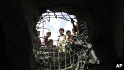 Boys look through a hole made by a Saudi-led airstrike on a bridge in Sana'a, Yemen, March 23, 2016.