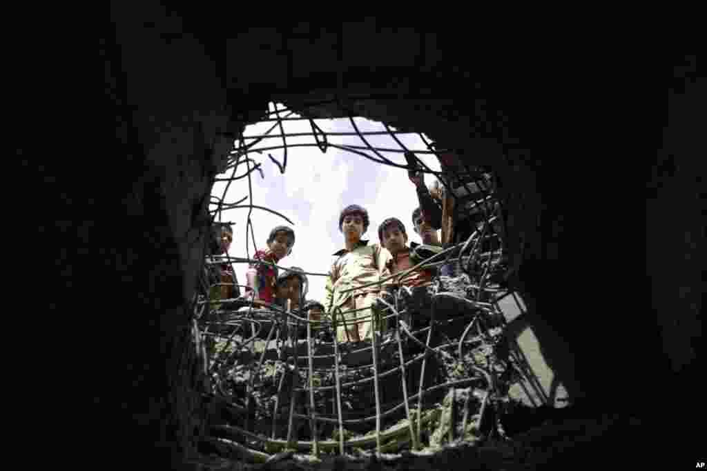 این بچه ها به سوراخی نگاه می کنند که براثر حمله جنگنده های عربستان در صنعا در یمن ایجاد شده است.