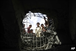 FILE - Boys look through a hole made by a Saudi-led airstrike on a bridge in Sanaa, Yemen, March 23, 2016.
