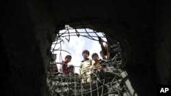 صنعا میں ایک پل پر سعودی فضائی کارروائی سے ہونے والے سوراخ سے بچے نیچے جھانک رہے ہیں۔