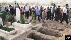 Mourners walk past open graves at a cemetery during the funeral for four people killed in a raid by government forces in a neighborhood of Damascus, Syria, April 5, 2012