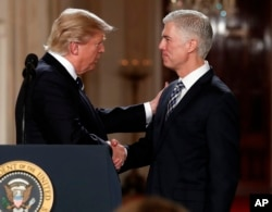 FILE - President Donald Trump shakes hands with 10th U.S. Circuit Court of Appeals Judge Neil Gorsuch, his choice for Supreme Court associate justice in the East Room of the White House in Washington, Jan. 31, 2017.