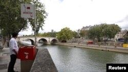 Seorang wartawan berpose di dekat tempat BAK ramah lingkungan yang dicat merah di Ile Saint-Louis di pinggiran Sungai Seine, Paris, Perancis, 13 Agustus 2018.