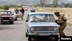 8일 우크라나이 남부 마리우폴 검문소에서 정부군 병사들이 차량을 검문하고 있다.