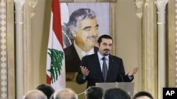 Lebanese caretaker Prime Minister Saad Hariri speaks during a press conference with a poster of his slain father Rafik Hariri in the background, in Beirut, Jan. 20, 2011