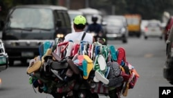 A man sells rubber flip-flops on his motorcycle in Manila, Philippines, 2013. (AP Photo/Aaron Favila)