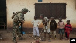 A French soldier talks to curious children as he mans a roadblock in the Miskine neighborhood of Bangui, Central African Republic, Jan. 6, 2014.