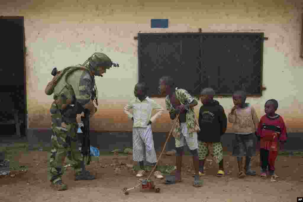 A French soldier talks to curious children as he mans a roadblock in the Miskine neighborhood of Bangui, Central African Republic.