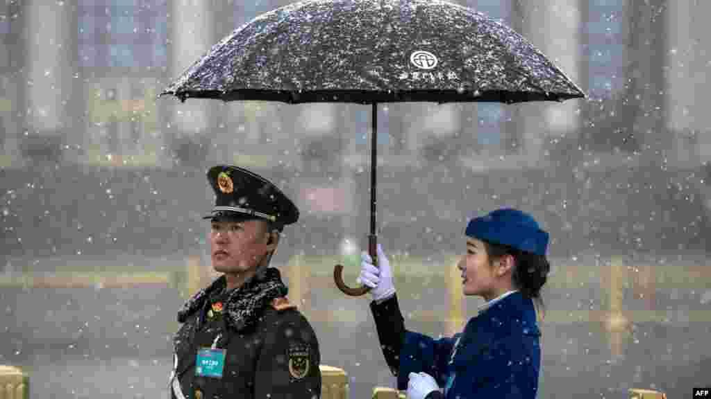 中国人大会议期间,人民大会堂外面,一位女服务员摆拍照片,在降雪时为武警打伞。(2018年3月17日)