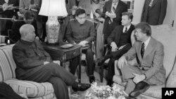 1977年2月8日,美国总统卡特及其国家安全顾问布热津斯基在白宫总统办公室会见中国驻美国联络处主任黄镇(前排左一)