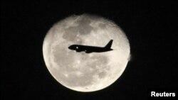 Một máy bay phản lực chở hành khách bay trước mặt trăng