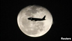 A passenger jet flies in front of the moon in Bogota, Colombia on Nov. 1, 2012.