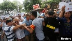 Cảnh sát cố ngăn chặn người biểu tình phản đối vụ cá chết hàng loạt ở miền Trung, Hà Nội, ngày 1/5/2016.