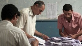 Egyptian election workers count the ballots following the end of the two day presidential election at a school in Cairo, Egypt. Experts say the elections were fairly clean given Egypt's past corruption.