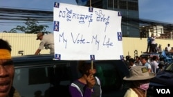A protester holds a sign during an 20,000-strong rally organized by the Cambodia National Rescue Party on Saturday, September 07, 2013, a day before the official announcement, demanding an investigation into irregularities and an accurate reflection of voters whom it says were left out of the process.