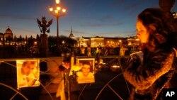 ຜູຍິງຄົນໜຶ່ງຢືນເບິ່ງຮູບ ຢູ່ບ່ອນໄວ້ອາໄລ ບັນດາຜູ້ເຄາະຮ້າຍ ຈາກ ເຮືອບິນຕົກ ທີ່ຈະຕຸລັດ Dvortsovava ນະຄອນ St. Petersburg.