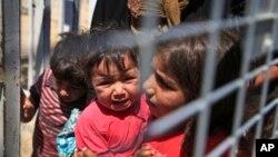 Un enfant syrien porte un bébé a la frontière turque, juin 2015. Image: AP