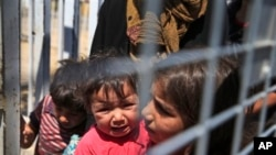 在边境关口等待从土耳其被送回叙利亚的小难民。(2015年6月17日)