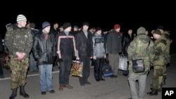 Russians, back to camera at right, and Ukrainians prepare for an exchange of prisoners outside Donetsk in eastern Ukraine, Friday Dec. 26, 2014.