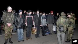 Người Nga, bên phải quay lưng về phía máy chụp hình, và người Ukraine chuẩn bị trao đổi tù binh bên ngoài Donetsk ở miền đông Ukraine, ngày 26 tháng 12, 2014.